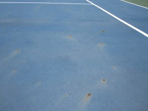 What causes rust spots on a tennis court